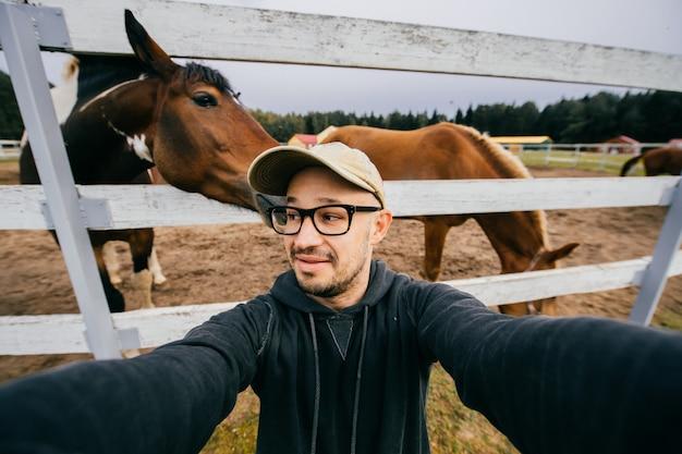 彼の後ろに馬とselfieを取って変な男。