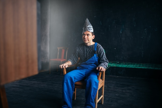 Funny man in tinfoil hat sits in chair, paranoia concept. ufo, conspiracy theory, brain theft protection, phobia