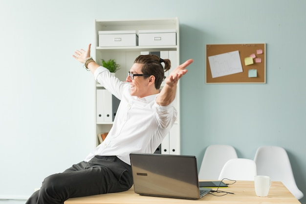 Funny man in white shirt sitting on wooden table in office