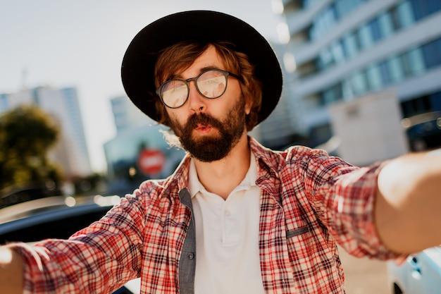 Uomo divertente con la barba che fa autoritratto dalla macchina fotografica mentre viaggia nella grande città moderna in asia.