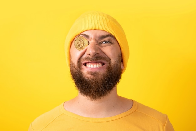노란색 배경 위에 비트코인을 가진 재미있는 남자