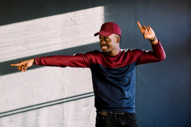 Funny man with dark skin gestures happily feels proud of his success, smiles gladfully, wears old fashionable red cap isolated over dark background. people, happiness and joy concept