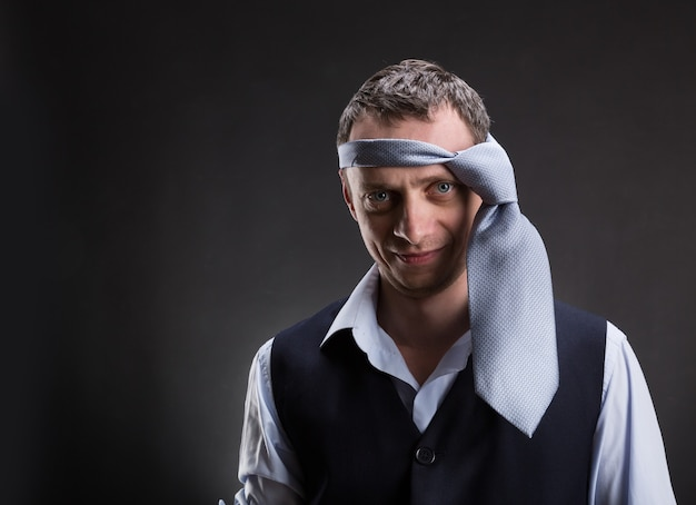 Funny man with necktie on his head over grey