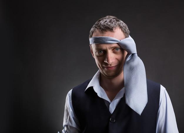 Забавный человек с галстуком на голове над серым