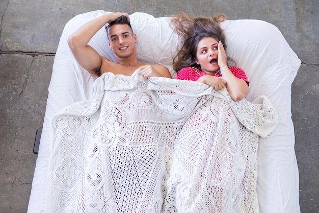 Funny married couple lying in bed and hiding under white blanket, looking at camera with eyes full of joy.