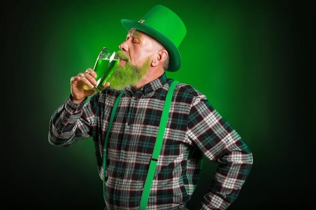 Забавный зрелый мужчина с бокалом пива на зеленом. празднование дня святого патрика