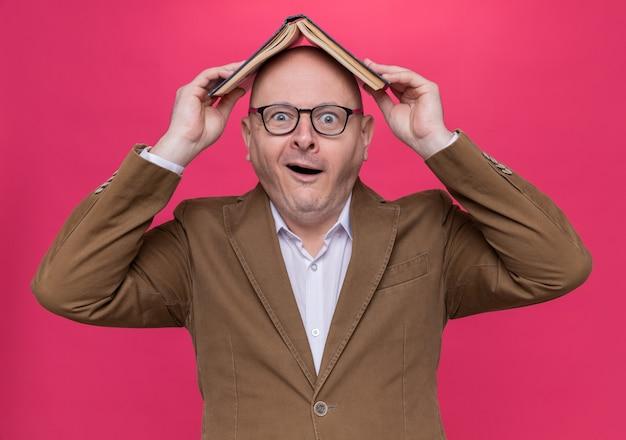 Uomo calvo di mezza età divertente in vestito con gli occhiali che tengono il libro aperto sopra la sua testa sorridente che sembra sorpreso in piedi sopra il muro rosa