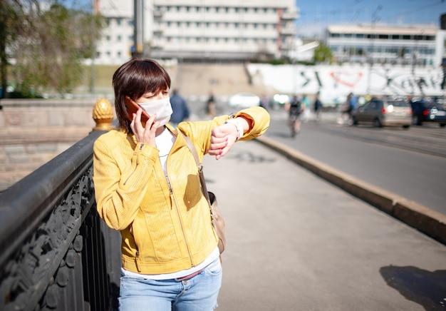 暖かい春の日に街を歩きながらスマートフォンで話している白い保護マスクの面白い中年女性。コロノウイルスのパンデミックとリモート通信の概念