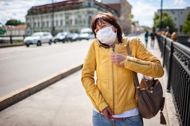 スマートフォンで話している白い保護マスクの面白い中年女性