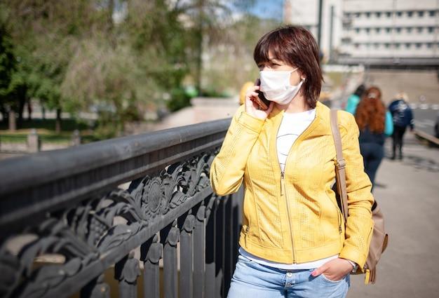 街を歩きながらスマートフォンで話している白い保護マスクの面白い中年女性