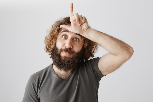 Funny middle-eastern guy mocking person with loser sign on forehead