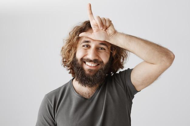 額の中の敗者のサインで人をあざける面白い中東男