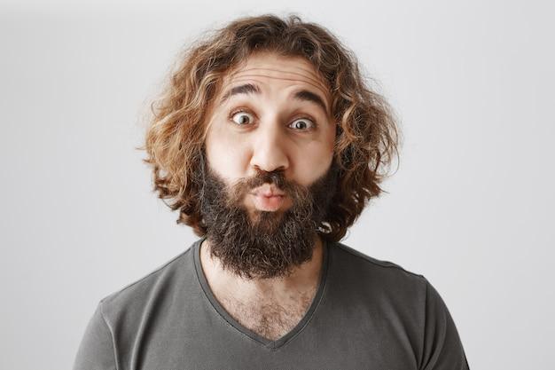 面白い中東の男性がキスをするために目を広げてふくれっ面をする
