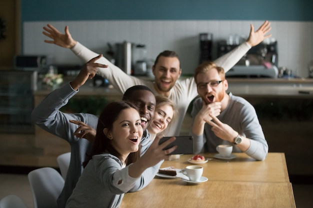 Funny millennial friends taking group selfie on smartphone in cafe