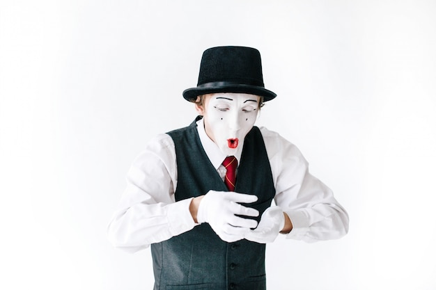 Funny mime in black hat looks at something invisible in his arms