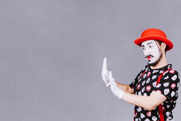 Смешная пантомима позирует возле серого