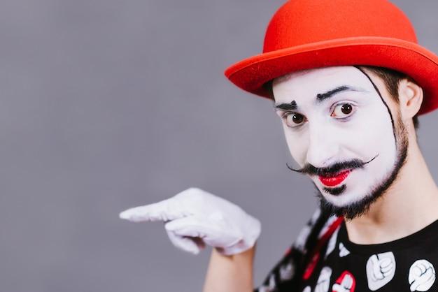 Funny mime posing near a gray