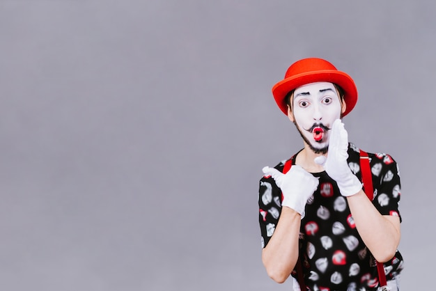 Funny mime posing near a gray