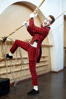Funny mime in a red suit pulls a rope