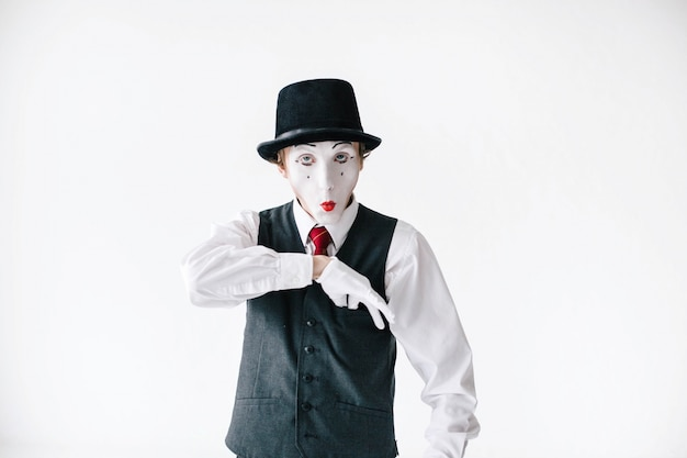 Funny mime takes something from pocket on his waistcoat