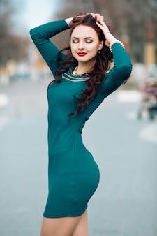 Забавная модель в солнечных очках и в маленьком зеленом платье