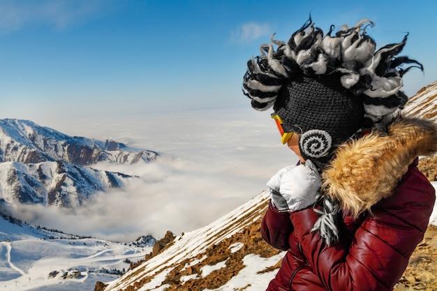 山の旅で面白いモヒカン刈りの帽子の女性。冬の旅行シーン、放浪癖のコンセプト。