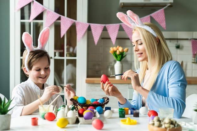 Funny moher and son wearing in bunny ears is painting easter eggs. a basket with colorful eggs on the table