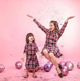 面白いお母さんと透明なスタイリッシュな椅子のピンクの壁に座っている子。小さな女の子と母親の風船と紙吹雪を楽しんで