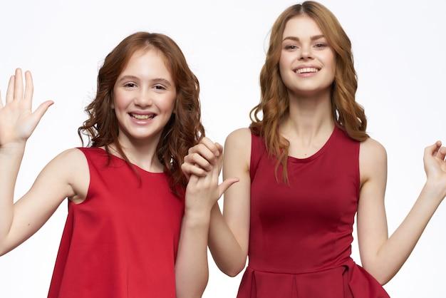 面白いママと娘は赤いドレスファッション明るい背景を抱擁します