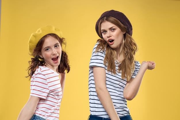 帽子をかぶっている面白いママと娘ファッション楽しい喜び家族黄色