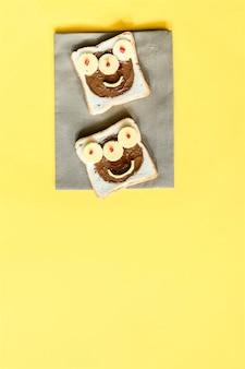ピーナッツバターとハロウィーンのサンドイッチトーストパンの面白いモンスターの顔、ナプキン黄色の背景のチーズがクローズアップします。キッズチャイルドスイーツデザート朝食ランチフード。