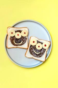 ピーナッツバター、プレートの黄色の背景にチーズとハロウィーンのサンドイッチトーストパンの面白いモンスターの顔がクローズアップします。キッズチャイルドスイーツデザート朝食ランチフード