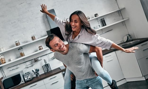 台所で若いカップルの面白い朝。彼のかわいいガールフレンドと時間を過ごす笑顔のひげを生やした男。