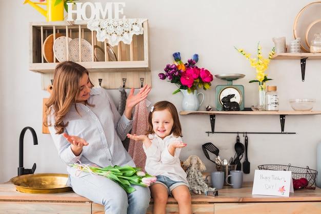 Смешная мать и дочь с тюльпанами, сидя на столе