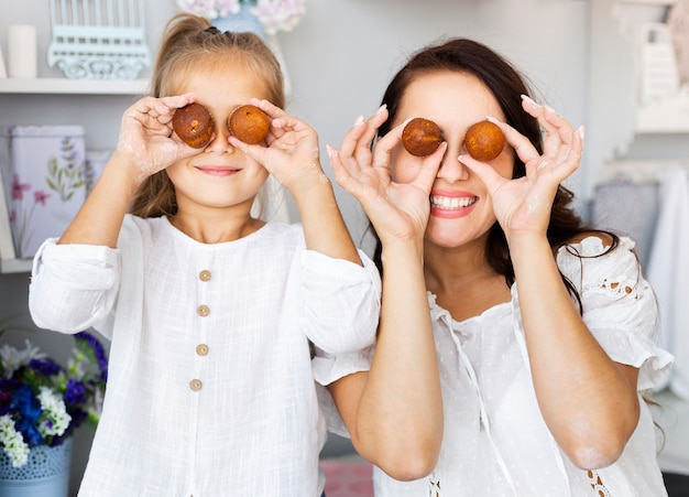 Funny mother and daughter making egg eyes