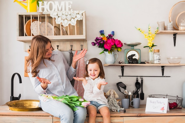 Funny mother and daughter with tulips sitting on table