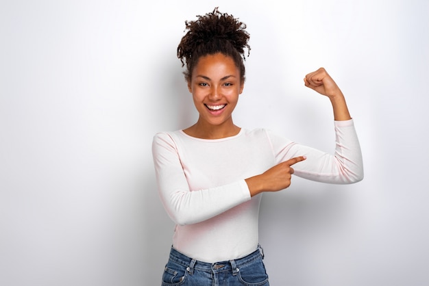 Funny mulatto girl pointing to an herself biceps smiling looking at the camera