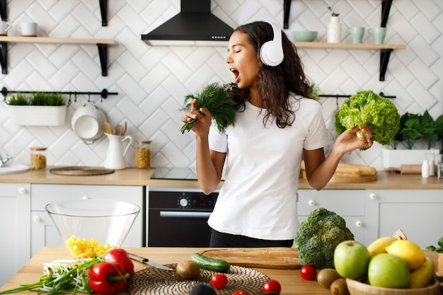 Funny mulatto woman in big wireless headphones is singing on imaginary greenery microphone on the modern kitchen near table full of vegetables and fruits