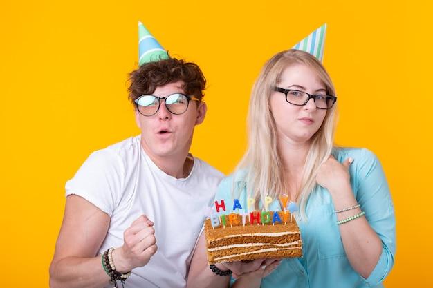 Забавный ботаник мужчина и женщина в праздничных кепках и очках держат праздничный торт со свечами