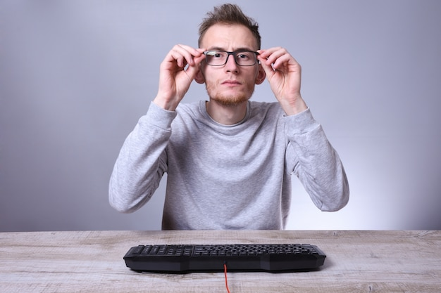 Funny nerd young businessman, man working on computer. typing on the keyboard programmer in glasses in front of computer.