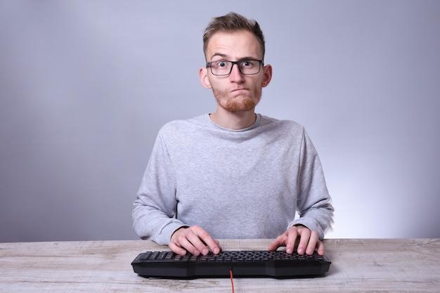 Бизнесмен смешного болвана молодой, человек работая на компьютере. вводить на клавиатуре программист в стеклах перед компьютером.