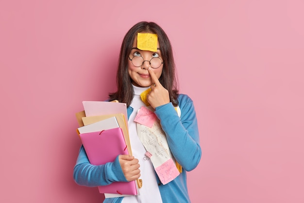 Funny nerdy student touches nose has sticky note with graphic stuck on forehead holds folders and papers concentrated above prepares for examination session. woman studies papers with sums in office.