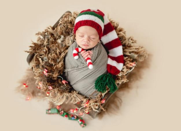 Funny newborn holding candy