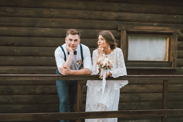 Funny newly married couple, smiling bride brunette young woman with the boho style bouquet with groom