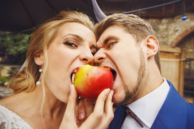 Funny newlyweds try to bite the same apple
