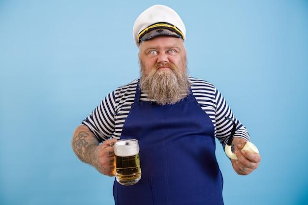 エプロンと面白い肥満の船乗りは、水色の背景にパイプとおいしいビールを保持します