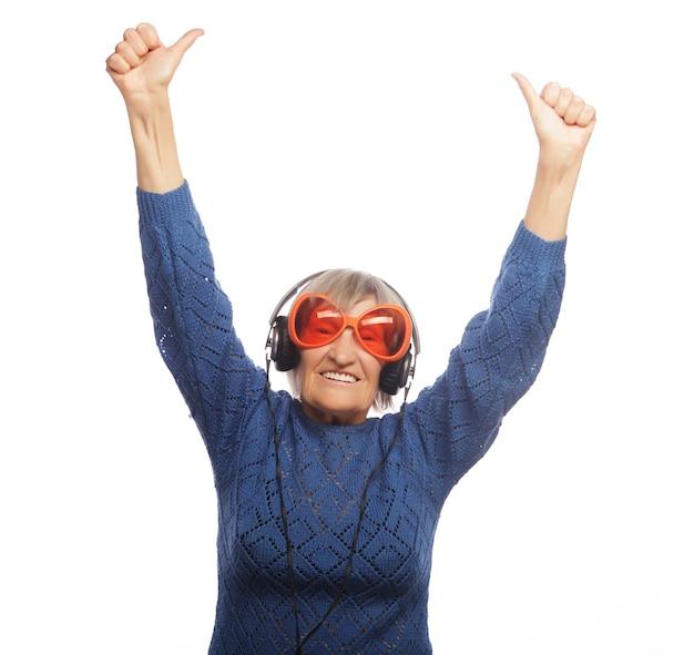Смешная старушка слушает музыку и показывает палец вверх. изолированные на белом.