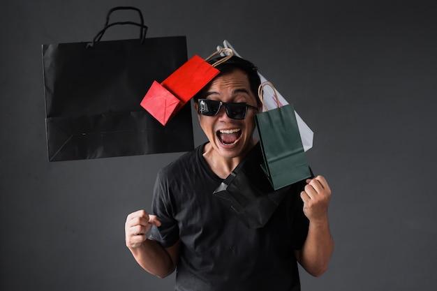 ショッピングバッグを持つ愚かな表現の買い物中毒の男と面白いオンラインショッピングの販売促進