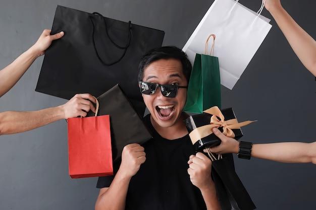 買い物かごを持っている多くの手による愚かな表現買い物中毒の人との面白いオンラインショッピング販売
