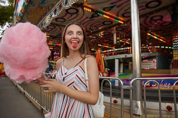 놀이 공원을 통해 포즈를 취하는 가벼운 여름 드레스에 긴 머리를 가진 재미 있은 열린 눈의 갈색 머리 여성, 행복하게보고 솜사탕을 먹은 후 분홍색 혀를 보여주는